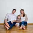 Happy family sitting on the floor against the wall — Stock Photo #13790273