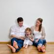 Happy family sitting on the floor against the wall and using tablet compute — Stock Photo #13790313