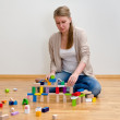 Stock Photo: Young woman building a tower with wooden blocks