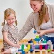 Little girl and young woman having fun playing with building blocks on the — Stock Photo #13790410