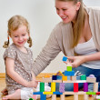 Little girl and young woman having fun playing with building blocks on the — Stock Photo
