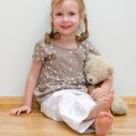 Cute little girl sitting with teddy bear on the floor against the wall — Stock Photo #13790442