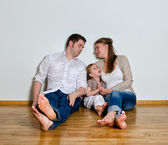 Happy family sitting on the floor against the wall — Stock Photo