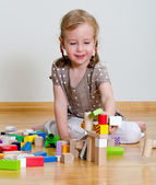 Cute little girl sitting on the floor and playing with building blocks — Stock Photo