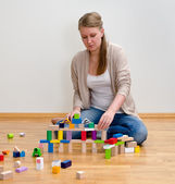 Young woman building a tower with wooden blocks — Stock Photo