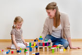 Cute little girl and young woman sitting on the floor and playing with buil — Stockfoto
