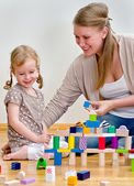 Little girl and young woman having fun playing with building blocks on the — Stok fotoğraf