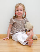 Cute little girl sitting with teddy bear on the floor against the wall — Stock Photo