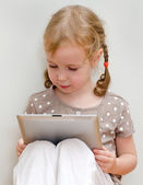Cute little girl sitting against the wall and using tablet computer — Stock Photo