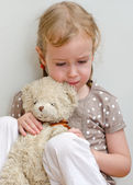 Sad lonely little girl sitting with teddy bear near the wall — Stock Photo