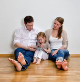 Happy family sitting on the floor against the wall and using tablet compute — Stock Photo