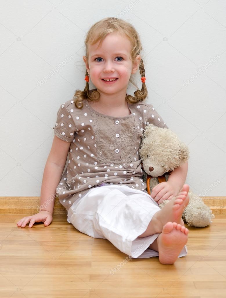 Cute Little Girl Sitting With Teddy Bear On The Floor
