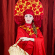 Woman in russian traditional clothes with basket — Stock Photo #15383133