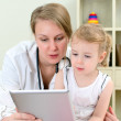 Pediatrician and little girl using tablet computer — Stock Photo #16309353