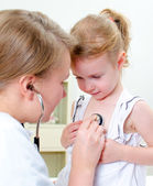 Female doctor examining little girl with stethoscope — Stock Photo