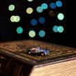 Old book and miniature car on bokeh lights background — Stock Photo #16922319
