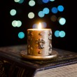 Royalty-Free Stock Photo: Burning candle and old book on bokeh background