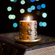 Stockfoto: Burning candle and old book on bokeh background