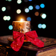Burning candle and seasonal decorations on bokeh lights background — Stock Photo