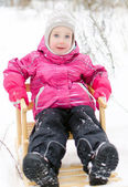 Cute little girl sitting in sled in the park — Stock Photo