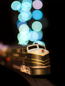 Miniature train on a christmas lights bokeh background — Stock Photo