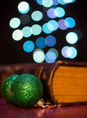 Old book and seasonal decorations on bokeh lights background — Zdjęcie stockowe
