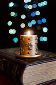 Burning candle and old book on bokeh background — Stock Photo