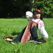 Pretty woman in russian traditional costume sitting on the grass — Foto de Stock