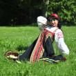 ロシアの伝統的な衣装を草の上に座っているきれいな女性 — ストック写真