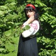 Pretty woman in russian traditional costume in the park — Stok fotoğraf