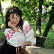 Portrait of pretty woman in russian traditional costume in the park — Stock fotografie
