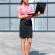Attractive girl with notebook in front of office building — Stock Photo #17854071