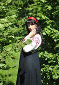 Pretty woman in russian traditional costume in the park — Stock Photo