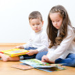 Little boy and girl sitting on the floor and reading a book — Stock Photo