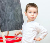 Little boy standing near blackboard — Stock Photo