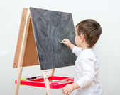 Little boy drawing on blackboard — Stock Photo