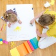 Young woman and little girl drawing together sitting on the floor. Top view - Foto Stock