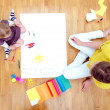 Young woman and little girl drawing together sitting on the floor. Top view — Stock Photo #19016451