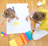 Young woman and little girl drawing together sitting on the floor. Top view — Stock Photo