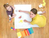 Young woman and little girl drawing together sitting on the floor. Top view. — Stock Photo