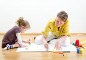 Young woman and little girl drawing together sitting on the floor — Stock Photo