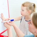 Pretty little girl with teacher near whiteboard — Stock Photo