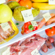 Open fridge full of fruits, vegetables and meat with marked calories — Stock Photo