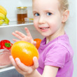 Happy smiling little girl holding orange on open fridge background — Stock Photo