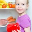 Happy smiling little girl holding paprika on open fridge background — Stock Photo