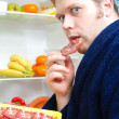 Handsome man eating ham slice near open fridge - Stock fotografie