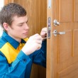 Royalty-Free Stock Photo: Young handyman in uniform changing door lock