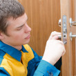 Young handyman in uniform changing door lock - Stock Photo