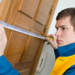 Young handyman in uniform working with measure tape — Stock Photo #20419263