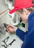 Plumber in uniform repairing pipeline in the house. — Stock Photo